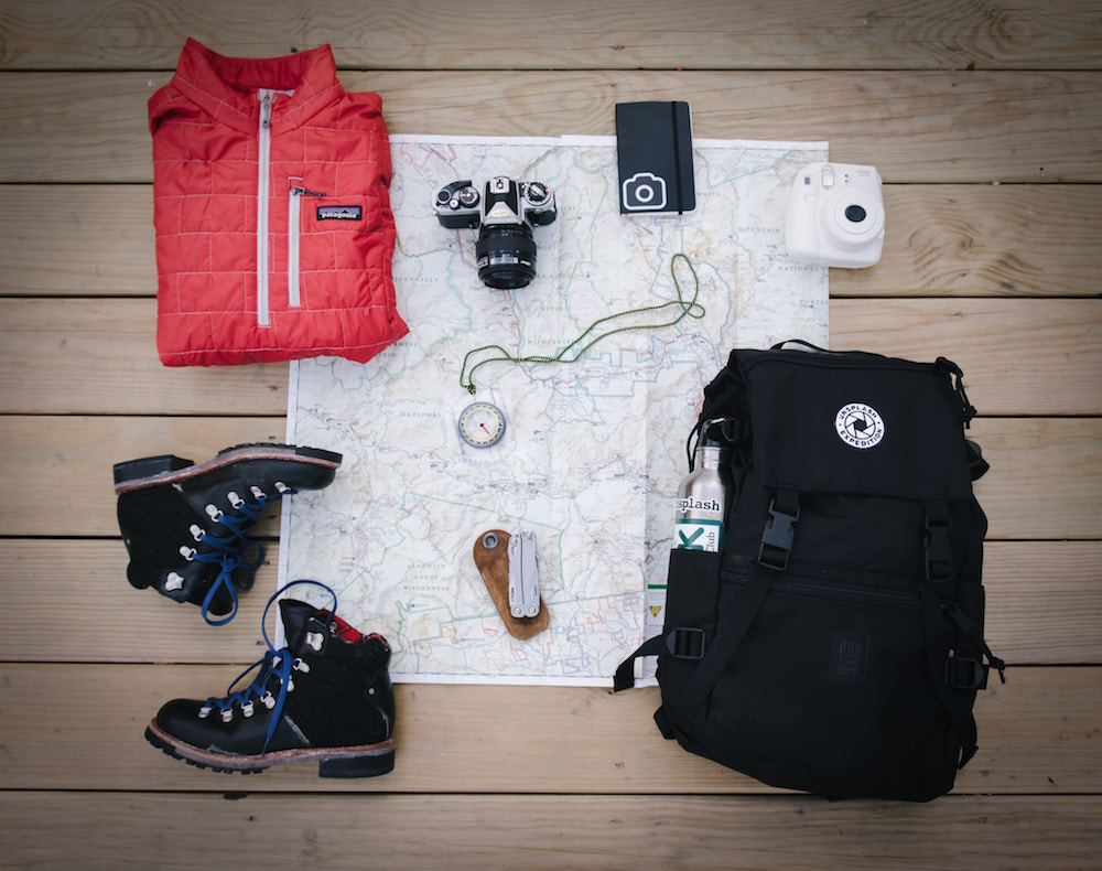 Hiking boots, backpack, camera, map and other items on the floor