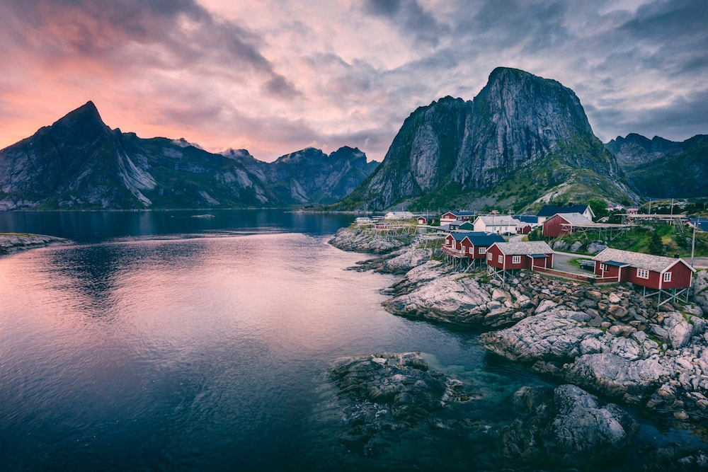 Red houses set in a magnificent scenery of majestic mountains and fjords