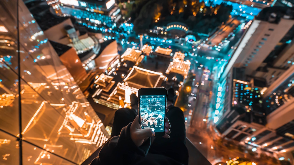 Person shooting city lights with a smartphone from a building
